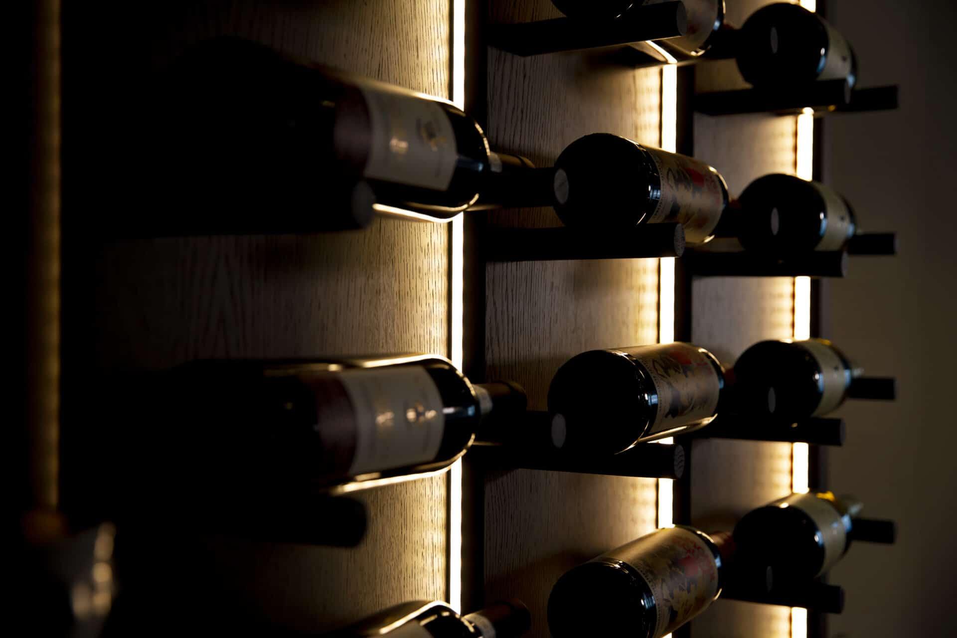 Närbild på vinflaskor med belysning mörkbetsad ek